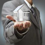 Business man present  diamond house model